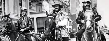 (Photo: Luciano Pavarotti on a horse, flanked by two mounted New York City police officers.)